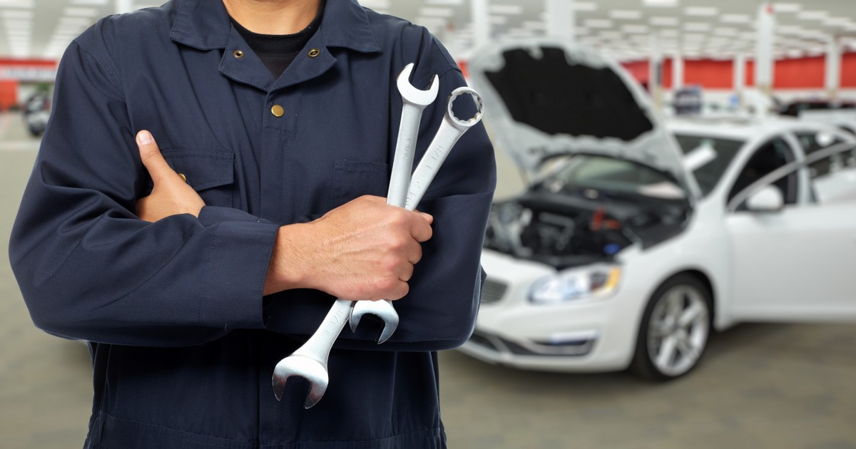 mechanic holding two wrenches